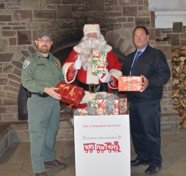 Santa Claus joins Erie County Park Ranger Chuck Bartlett (left) and Erie County Parks Commissioner Daniel J. Rizzo (right) at the Chestnut Ridge park casino to announce the return of Santa Land to the park. Guests are encouraged to help brighten a child's holiday by donating a new, unwrapped toy in one of the Toys for Tots barrels.
