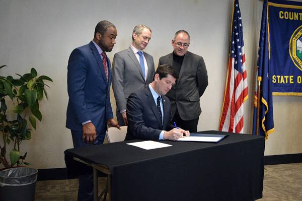 Erie County Executive Mark C. Poloncarz (seated at table) signs an executive order creating a county website to publicize the ranking of nursing homes in Erie County. Observing the signing, from left: Erie County Commissioner of Senior Services Tim Hogues, New York State Assemblyman Sean Ryan (149th District) and Erie County Commissioner of Social Services Al Dirschberger.