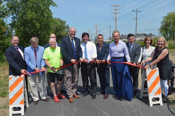 Erie County Executive Mark C. Poloncarz (center, white shirt) joins elected officials, partners and supporters of the Tonawanda `Rails to Trails` project to cut the ribbon and officially open the trail to the public.