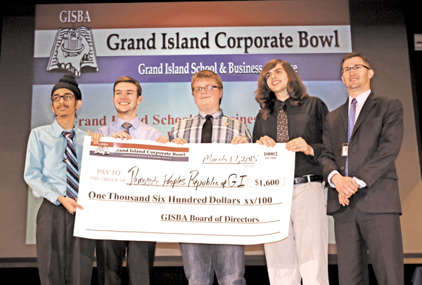 Pushpinder Singh, Andrew Colautto, Ryan Marlin, Devlin McMaster accept a check for $1,600 from Grand Island High School Assistant Principal Michael Carter after winning the 2015 Corporate Bowl on Tuesday in the Grand Viking Theater. (Photo by Larry Austin)