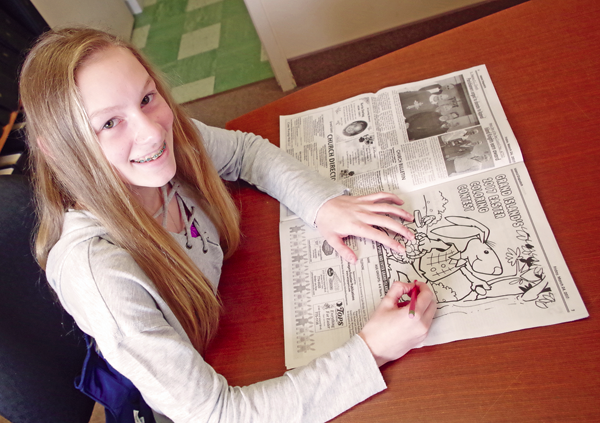 Anna Bartlo of Grand Island checks out the new Easter Coloring Contest entry in last week's Island Dispatch.