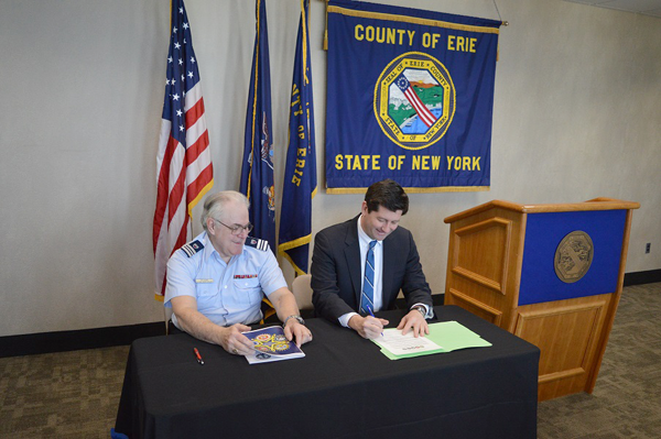 Erie County Executive Mark C. Poloncarz (seated at right) signs a proclamation honoring local military veterans as part of Armed Forces Week celebrations. The county executive was joined by Bill Callahan (seated, left), public affairs officer for the WNY Armed Forces committee. Poloncarz was the first to sign the proclamation, which Callahan will take to the county executive's counterparts in the eight counties of Western New York for their signatures.