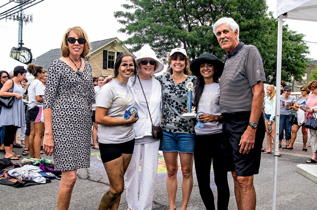 Vicki Fuerch, far left, and her husband John Fuerch, far right, of VicTree Coins & Collectibles, presented Grand Island High School's winning Chalk Walk mural team a pure silver coin at the Lewiston Art Festival on Saturday. Also pictured are, from left, student Lex Hy, Chalk Walk chair Fay Northrop, GIHS teacher Megan Gaiek and student Lovepreet Kaur. Not pictured is the third member of the three-student team, Kelsey Mahoney. (Photo by Wayne Peters; click to enlarge)
