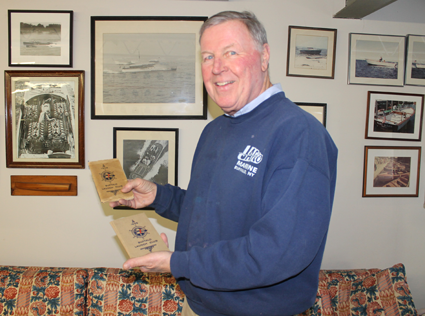 Buffalo Launch Club member Tom Frauenheim holds two club rosters, one from 1905 and one from 1908. These are among artifacts collected by the late Roswell Pfohl, former club member and historian. Contractor Paul Lunick found the documents last year while he was doing a barn demolition and clean out at Pfohl's former East River Road residence. (Photo by Karen Keefe)