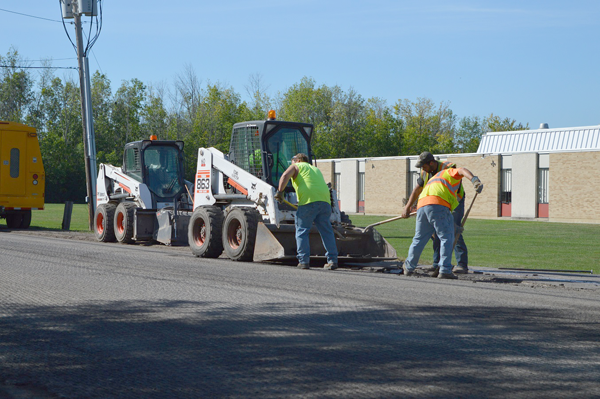 Erie County Highway crews work on the shoulders of Baseline Road near Whitehaven Road on Grand Island. The road has already been milled and will be overlayed with asphalt while similar work will begin on Whitehaven Road on Monday.