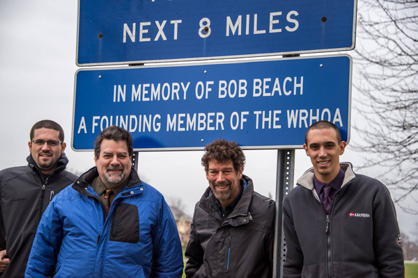 Signs honor the late Bob Beach on the Island's West River, near where he lived on West River Road. Pictured, from left, are Beach's grandson Robert Beach and his uncle Victor, Rob Beach and his son Jacob.