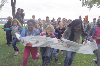 Children break through a paper banner to start the 2015 CROP Walk.