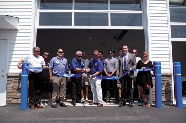 Chris Taylor, left, and Travis Smith, owners of Certified Autobrokers at 1693 Grand Island Blvd. cut the ceremonial ribbon on a new 2,200-foot building and an 8,000-square-foot parking lot at an event held July 6. They were joined in the ribbon-cutting by employees, members of the Grand Island Chamber of Commerce, and representatives of town government. (Photos by Larry Austin)