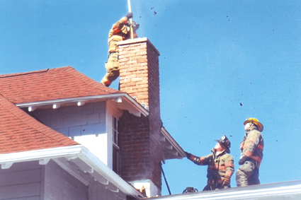 Grand Island firefighters work to put out a chimney fire at a home on West River Road Tuesday. (Photo by Ray Pauley)