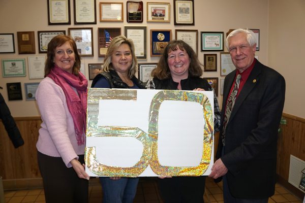 From left, the chamber's Liz Wilbert and Shannon Zaccaria visited dinner sponsors Niagara Frontier Publications with the 50th invite to Island Dispatch Account Executive Colleen Rebmann and Publisher Skip Mazenauer. (Photo by Larry Austin)