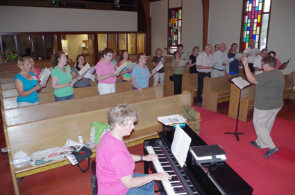 The Grand Island Community Chorus rehearses Tuesday at St. Timothy Lutheran Church under the direction of Carolyn Lokken, with Kathy DeGlopper on keyboard. The chorus will perform a free concert July 21. (Photo by Larry Austin)