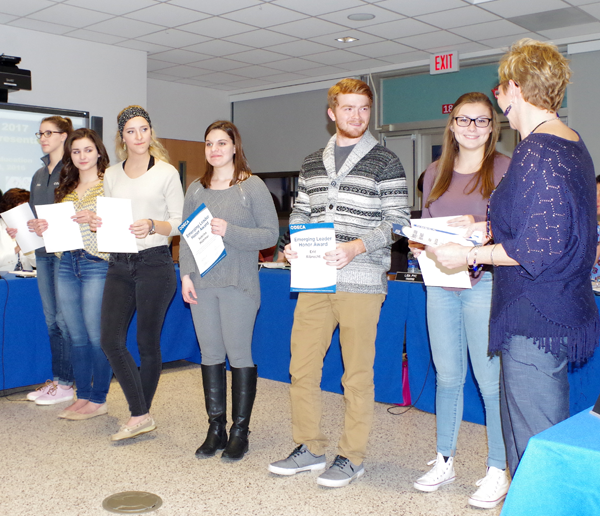 Grand Island High School business teacher announced at Monday's Board of Education meeting that nine students in the DECA program at the school have received the DECA Emerging Leader Honor Award. Chamberlain, far right, presented certificates to, from right: Natalie Braun, Eric Albrecht, Sabrina Mistriner, Kaitlyn Hoy, Maria Ramsperger and Cassidy Siebert. (Photo by Larry Austin)