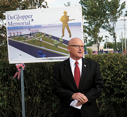 Patrick Soos of the DeGlopper Memorial Expansion Committee speaks during a groundbreaking ceremony last Thursday in front of a design of the proposed DeGlopper Memorial.