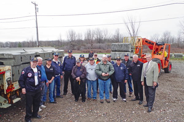 Veterans and members of the DeGlopper Memorial Expansion Committee were on hand Wednesday to see delivery of 1,600-pound concrete blocks, part of the expansion of DeGlopper Park. Present were members of the VFW Post No. 9249, American Legion Grand Island Post 1346; Chris Taylor of Certified Auto Brokers, LDC Construction, Toni Amantia, committee member and owner of Adrian's Custard & Beef neighboring the park, and project manager Dan Drexelius. (Photo by Larry Austin)