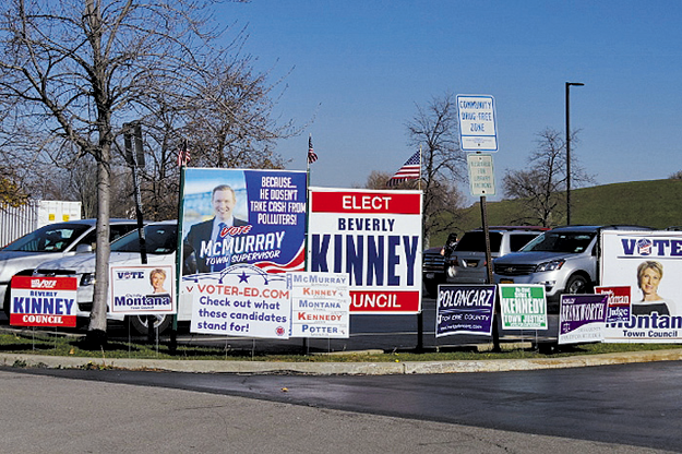 Campaign signs were a common sight at Island polling places Tuesday, including outside of the Grand Island Memorial Library, the polling place for districts 2 and 11. (Photo by Alice E. Gerard)