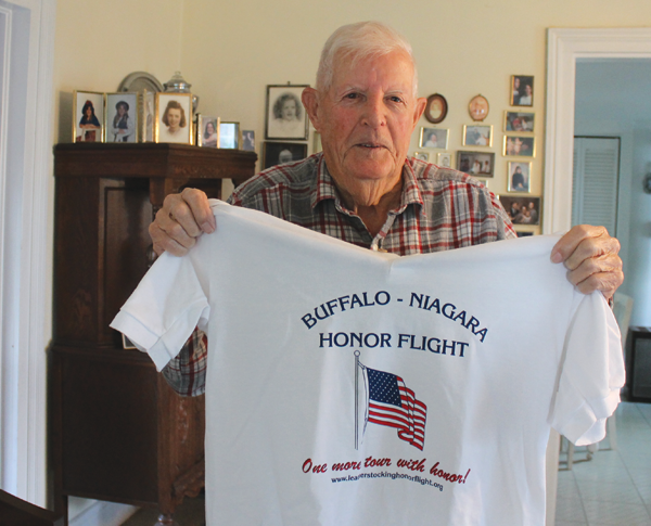 Army veteran Don Loder shows the T-shirt (back shown below) he'll be wearing when he departs on the Buffalo-Niagara Honor Flight this Saturday. The flights are arranged, free of charge, by the nonprofit Honor Flight program to make sure that World War II veterans get to see the monument built in 2004 in tribute to their military service. (Photo by Karen Carr Keefe)