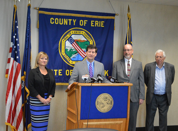 Pictured, from left: Town of Cheektowaga Councilmember Diane Benczkowski, Erie County Executive Mark C. Poloncarz (at podium), Village of Springville Mayor William Krebs and Town of Eden Supervisor Glenn Nellis announce the approval by New York of the countywide government efficiency plan. In total, 38 towns and villages collaborated with Erie County on the efficiency plan. With the plan's approval, homeowners will receive a rebate check next year if local governments and school districts implement an approved government efficiency plan that projects 1 percent tax levy savings for 2017-19 and adopt a 2016 budget under the property tax cap.
