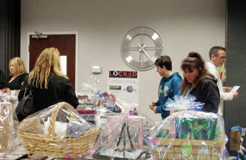 Browsers check out the baskets at a raffle fundraiser held by Fresenius Kabi of Grand Island. (Photo by Alice E. Gerard)