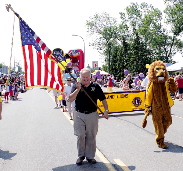 Henry Lobl carries Old Glory alongside Leo the Lion, mascot of the Grand Island Lions Club, during the Independence Day Parade Saturday. The Lions will hold their Special Kids Picnic Wednesday at the Buffalo Launch Club. (Photo by Larry Austin)