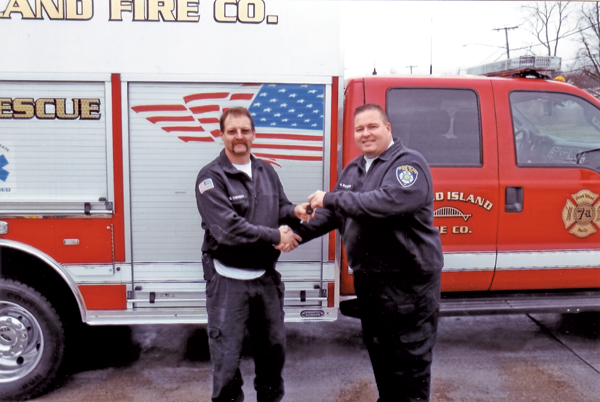 Grand Island Fire Co. Chief Matt Osinski, left, receives the keys to a new 2015 rescue vehicle from fire company Board of Directors Chairman Greg Butcher. (Photo by Ray Pauley)