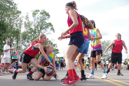 Grand Islander Chase Luthringer of The Avengers looks to pass from her knees as Kayla Callaghan of Full Court Hoops, a team from Buffalo, defends during play in the 13-14 age bracket of the Gus Macker 3-on-3 Tournament Saturday. (Photos by Larry Austin)