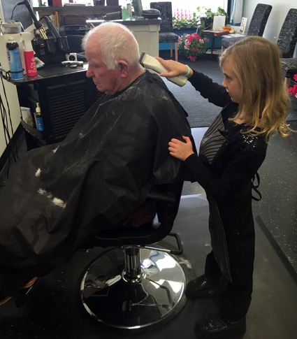Eden Fancher cuts the hair of her grandfather, Dayton Fancher, a veteran, on Veterans Day. (Photo by Cathy Fancher)