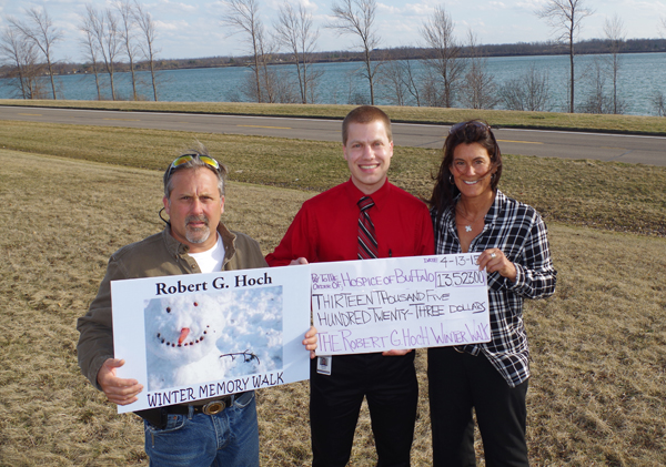 T.J. and Robin Hoch flank David Yacono, special events associate at Hospice Buffalo, during a presentation along the West River of a check for $13,523, the proceeds from the Robert G. Hoch Winter Memory Walk. The walk is a fundraiser for Hospice that T.J. and Robin run in memory of and in tribute to their late father. (Photo by Larry Austin)