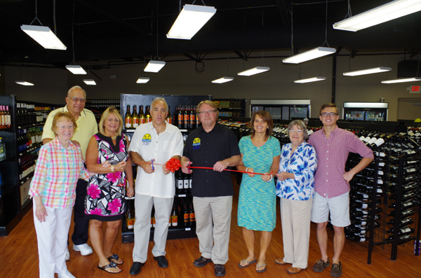Grand Islanders Jim Atkinson and Tom Corrao are surrounded by family and friends at the ceremonial ribbon-cutting to their business Friday. (Photos by Larry Austin)