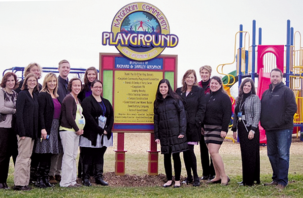 Members of the Kaegebein Playground Committee, teachers, and parents stand in front of the new Kaegebein Playground sign.
