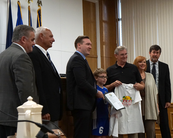 At the June 6 meeting in Town Hall, the board presented a proclamation to longtime KidBiz chairman Jim Sharpe, and current KidBizer Nathaniel Cohen. From left: councilmen Chris Aronica and Ray Billica, Town Supervisor Nathan McMurray, Cohen, Sharpe, and council members Bev Kinney and Mike Madigan. (Photo by Larry Austin)