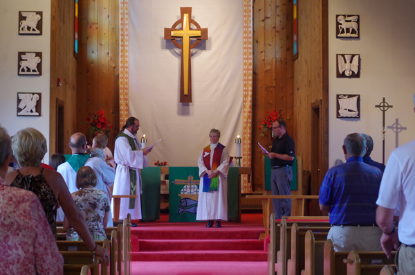 The Rev. Kris Bjerke-Ulliman, center, is installed as pastor of St. Timothy Lutheran Church during a ceremony officiated by Dean Pastor Lee Miller, left, and lay leader Ryan Cummings.