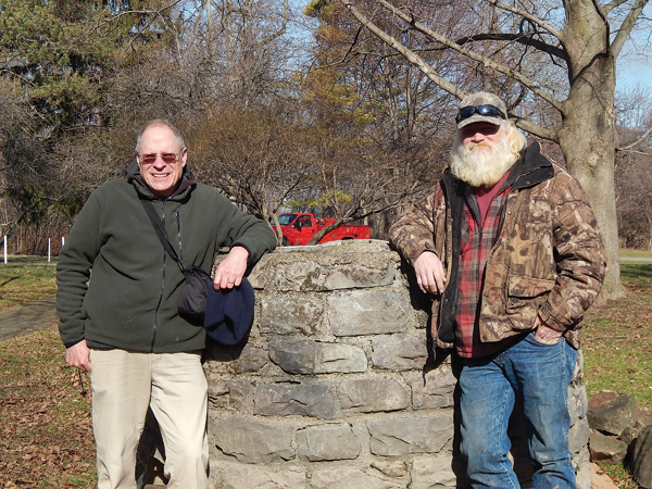 Islanders Paul Leuchner, left, and Jeff Dinsmore, flank the well recovered by Dinsmore's LDC Construction on Feb. 2. Leuchner, a retired Army Corps of Engineers biologist, spearheaded the project for the Grand Island Historical Society.