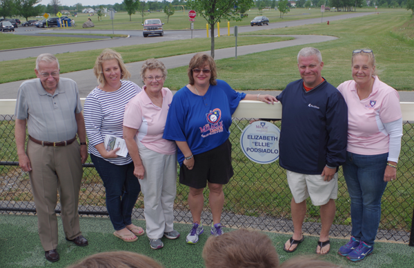 Family members of the late Ellie Podsiadlo gather at the left field fence in Miracle League Field for the installation of the ballplayer's name in the Miracle League Hall of Fame. Podsiadlo, Antonio Tallarico, and David D'Angelis were enshrined in the first induction class of the league's Hall of Fame Sunday during Opening Day events. The league for players with special needs began play Sunday. (Photos by Larry Austin)