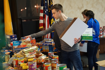 Josh Schaefer, DECA member, was one of 33 students from the school district to volunteer for the Neighbors Foundation at the Knights of Columbus Mary Star of the Sea Council hall.