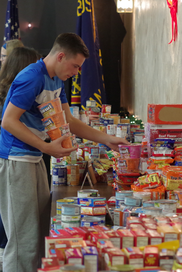 Tom Stedman of the Grand Island boys varsity soccer team sorts food donated by fellow Islanders for others in need.