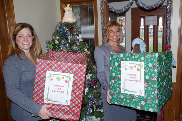 Bonnie FitzGerald, left, a real estate agent with RealtyUSA, and Shelia Ferrentino, assistant office manager with RealtyUSA, show the collection boxes at their office that will receive donations of food, clothing and toys for the needy. (Photo by Larry Austin)