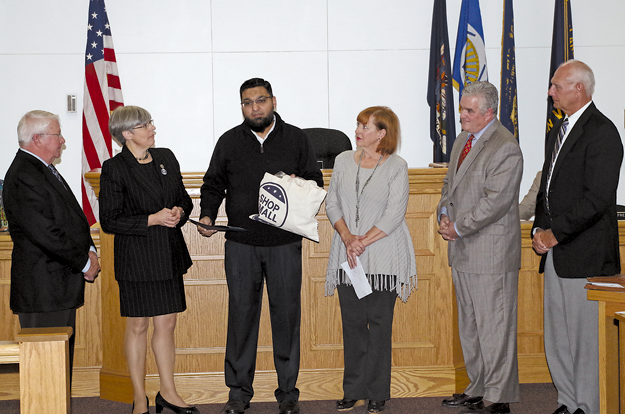 Island Ship Center's Fahim Mojawalla displays a `Shop Small` bag in accepting a town proclamation from the Grand Island Town Board at the Monday meeting in Town Hall. Town Supervisor Mary Cooke presented a town proclamation marking Small Business Saturday to Mojawalla and Bev Kinney, representing Grand Island Chamber of Commerce. They are joined by councilmen Gary Roesch, Chris Aronica and Ray Billica. (Photo by Larry Austin)