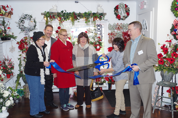 Andi LaMar cuts the blue ribbon on the ceremonial opening of Silk Florals, her business selling custom silk floral arrangements. Also at the ribbon-cutting ceremony were, from left, Nancy Gorrell, Pastor Calvin VanderMey of Bible Fellowship Center on Baseline Road, Dawn Fick, LaMar, Maria Beck, and Eric Fiebelkorn, president of the Grand Island Chamber of Commerce. (Photos by Larry Austin)