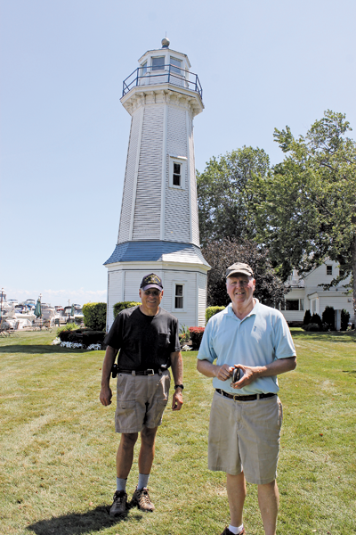 Paul Leuchner and Tom Frauenheim stand in front of the Buffalo Launch Club range light at 503 East River Road on Grand Island. The two are researching the origin of the lighthouse and seeking photos and recollections of those who may know about its history. They are planning an educational presentation on the lighthouse, where they will invite public input. (Photo by Karen Carr Keefe)