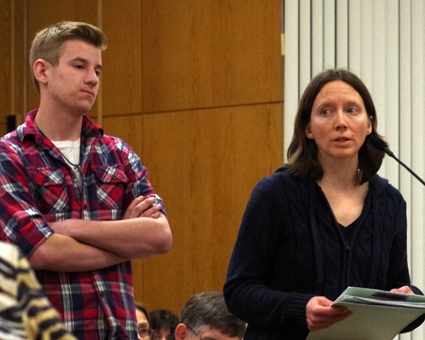 Josh Shipman listen to Nicole Gerber speak at the microphone during a public hearing on a proposal to amend the town's code regarding trapping of animals. (Photo by Larry Austin)