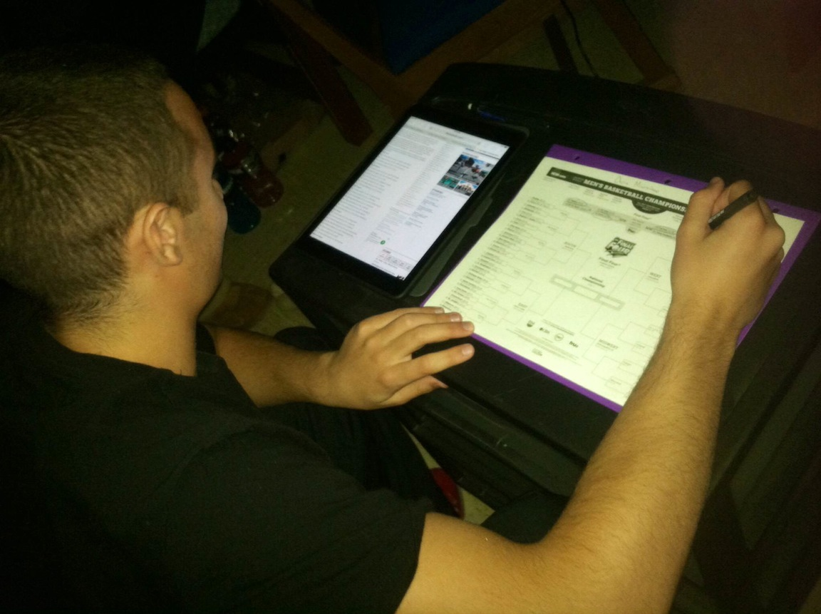 A Niagara University student filling out his bracket for March Madness.