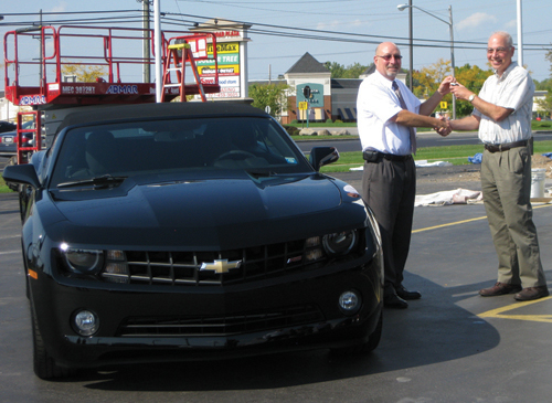 At Heinrich Chevrolet in Lockport, Henry Sadowski of the GM Professional Managers Network hands over the keys to a 2012 Chevrolet Camaro Convertible LT1 to first-prize winner James Grassi of Rochester.