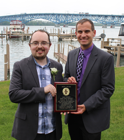 Joshua Maloni, managing editor at Niagara Frontier Publications, stands with Christian Hoffman, Community Missions Communications and Development Manager. Hoffman presented Maloni with a Public Relations/Media Award.