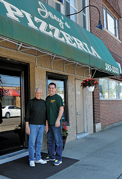 Joseph Previte, owner of Joey's Pizzeria, stands with his son, Mark, in front of his business on Buffalo Avenue. The two recently hung new flower baskets in front of the business.