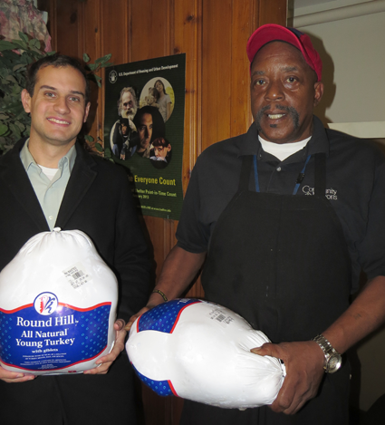 Community Missions Communications and Development Manager Christian Hoffman, left, holds one of the Thanksgiving turkeys chef Jimmie Walker will prepare for guests this holiday season.