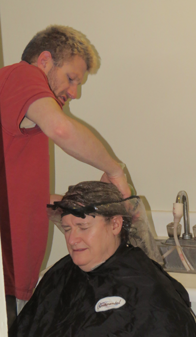 Lori Cooper receives free hair styling from Brian Palmer.