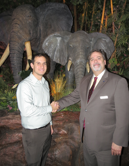 Community Missions Communications and Development Manager Christian Hoffman, left, shakes hands with Geoffrey Reeds, executive director of sales and marketing for Sheraton at the Falls. Guests are invited to dine at the Rainforest Café, pictured, on #GivingTuesday, when a portion of the proceeds will be donated to CMI.