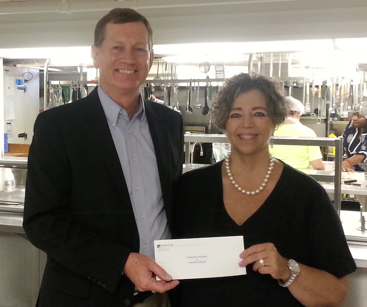 Mark O'Donnell, executive director of the Patrick P. Lee Foundation, presents a check to Robyn L. Krueger, executive director of Community Missions. Funds will be used to purchase food for the community soup kitchen.