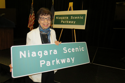 Mamie Simonson proudly displays the new parkway sign.