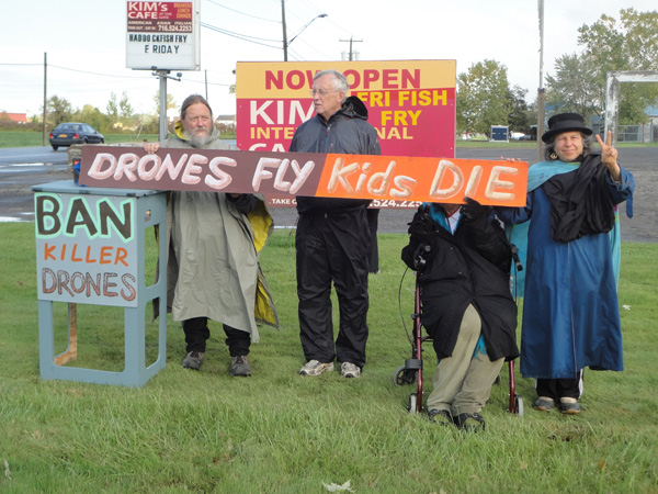 Pictured, from left, Russell Brown, Tom Casey, (behind sign) Valerie Kniederhoffer and Victoria Ross protest outside the Niagara Falls Air Reserve Base.